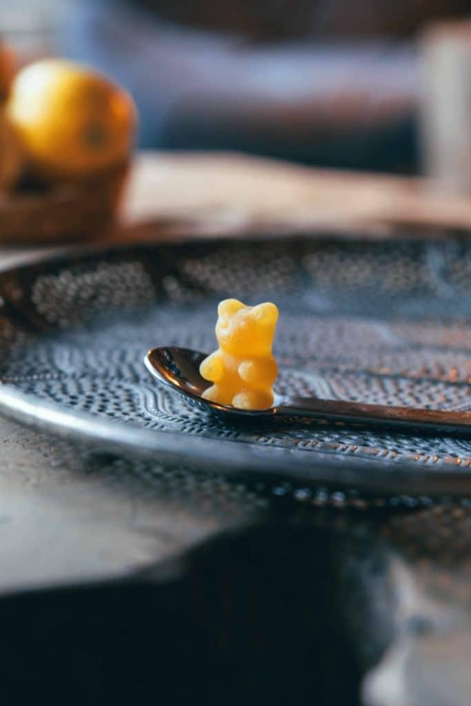 Ein Zitrone Ingwer Tee-Bär auf einem Teelöffel, darunter ist ein stylischer Servierteller, Tiefenschärfe, Teetrinken, TaTeeTaTa, Produkt Fotografie, WINGMEN Media