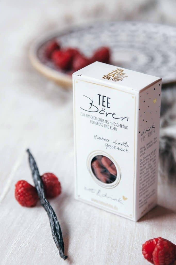 Eine Tee-Bären Verpackung, hell mit liebevollem Design, Typografie, Himbeere Vanille Geschmack Tee-Bären, Tisch mit Himbeeren und Vanilleschoten dekoriert, TaTeeTaTa, Produkt Fotografie, WINGMEN Media