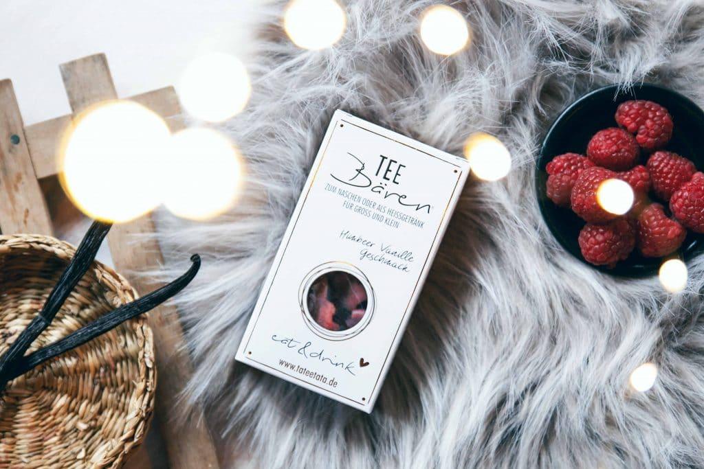 Topshot von einer Packung Tee-Bären mit Himbeer Vanille Geschmack auf einer kuschligen Decke, eine Schüssel Himbeeren, Vanilleschoten, Bokeh, Lichterkette, TaTeeTaTa, Produkt Fotografie, WINGMEN Media