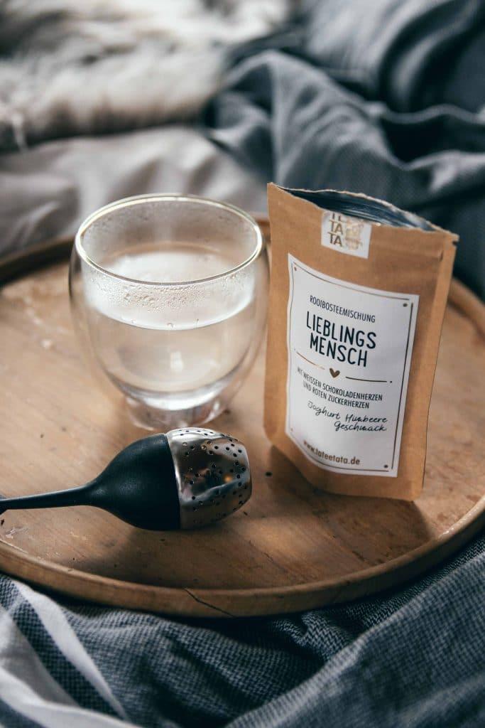 Eine geöffnete Tüte TaTeeTaTa Teemischung, Rooibos, ein heisses Glas Wasser und Teefilter auf einem Holztablett im Bett, TaTeeTaTa, Produkt Fotografie, WINGMEN Media