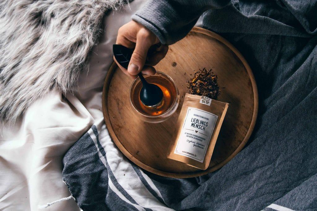 Eine offene Tüte LIEBLINGSMENSCH Rooibosteemischung mit Joghurt Himbeere Geschmack, und ein Glas Tee aus dem ein Teefilter herausgenommen wird, Decken im Bett, TaTeeTaTa, Produkt Fotografie, WINGMEN Media