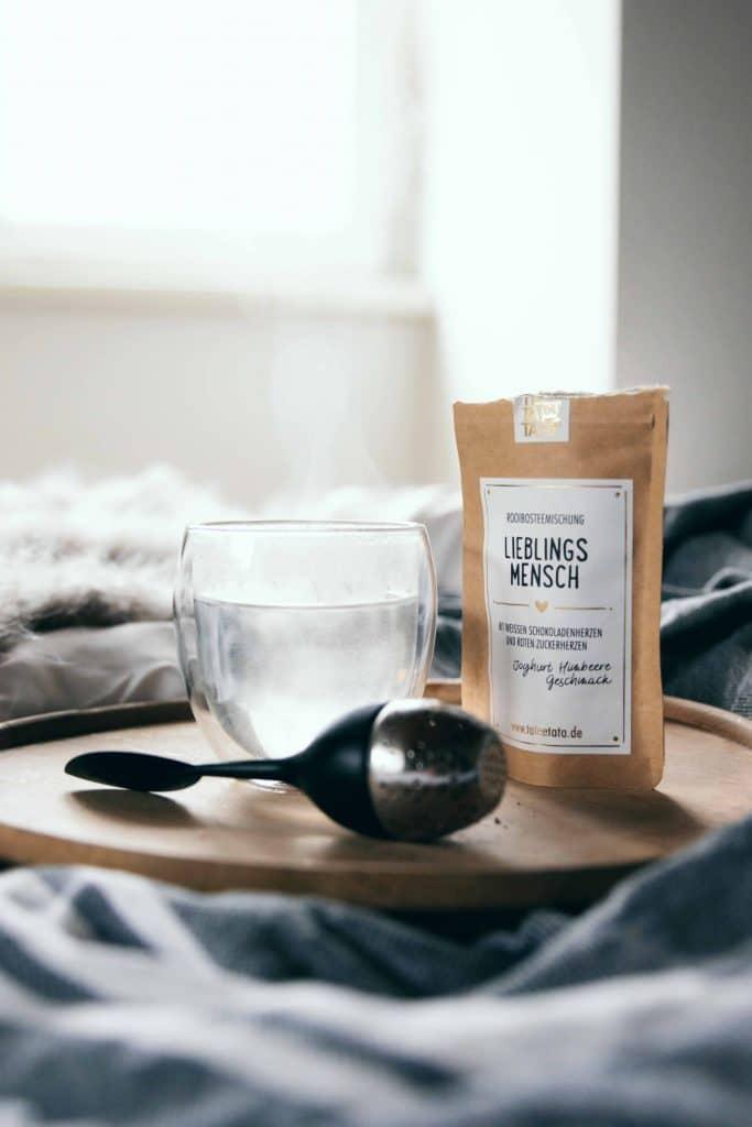 Ein heisses Glas Wasser in dem Dampf hochsteigt neben einer Tüte LIEBLINGSMENSCH Teemischung und einem Teefilter, auf einem Holztablett im Bett, gemütlich warm, Geschenk, TaTeeTaTa, Produkt Fotografie, WINGMEN Media