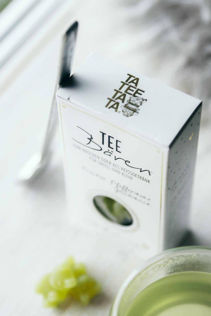 Eine Tee-Bären Verpackung von TaTeeTaTa mit frischem Pfefferminzgeschmack Tee-Bären, ein Glas Tee und Teelöffel, Heissgetränk, TaTeeTaTa, Produkt Fotografie, WINGMEN Media