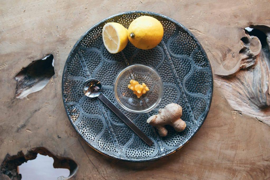 Topshot von einem Servierteller auf dem sich ein Glas mit Zitrone Ingwer Tee-Bären befindet, außen herum liegt eine Zitrone und Ingwer, Holztisch, TaTeeTaTa, Produkt Fotografie, WINGMEN Media