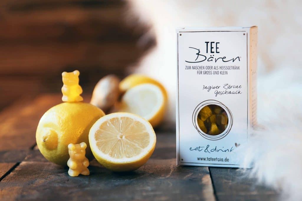 Eine Packung Tee-Bären neben einer aufgeschnittenen Zitronen und gelben Tee-Bären, eine kuschlig warme Decke und gemütlicher Holzboden, Tee-Bären zum Naschen oder als Teegetränk, Packshot, TaTeeTaTa, Produkt Fotografie, WINGMEN Media