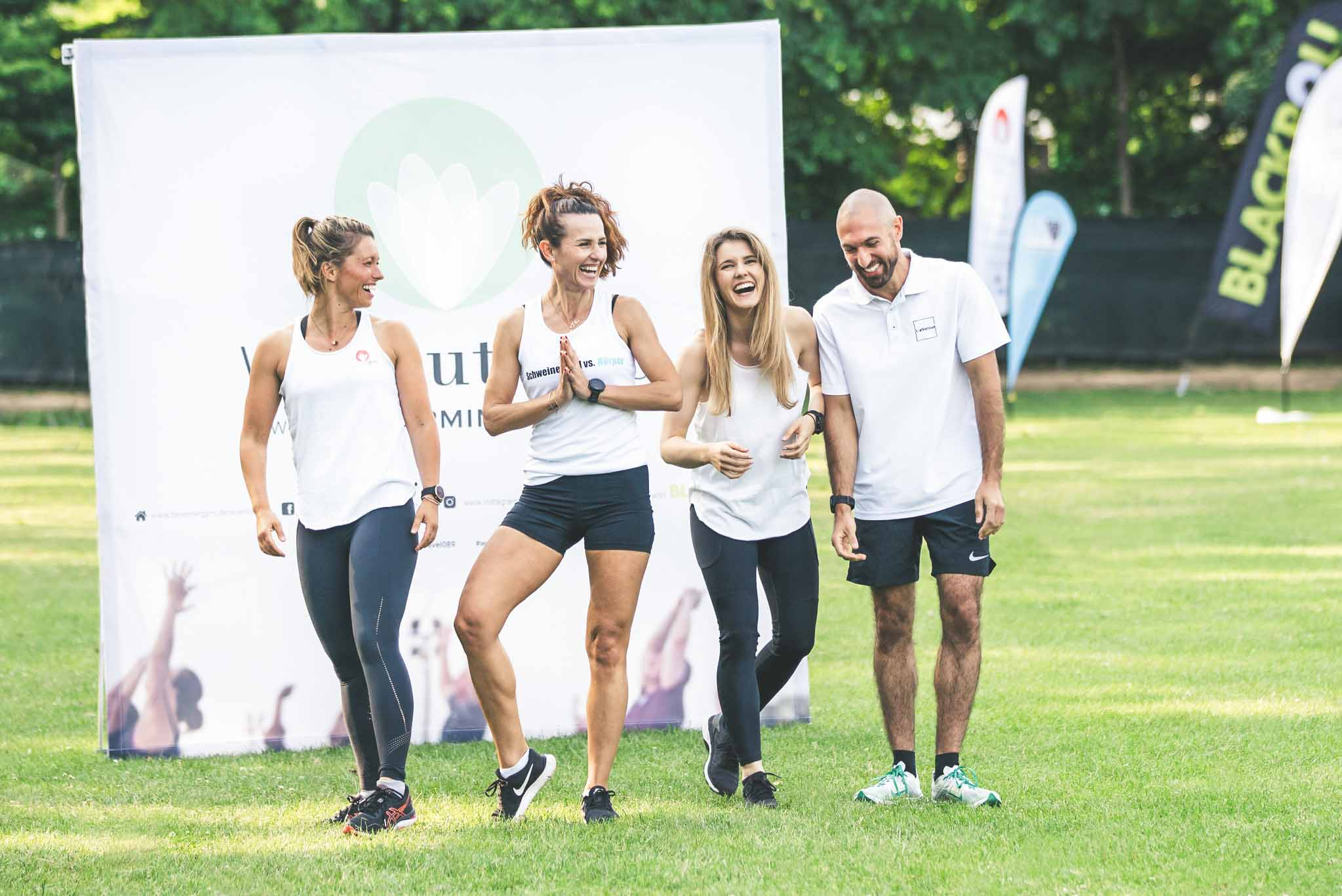 Vier lachende, sportliche Personen bei Outdoor Fitness Projekt Workoutside im Olympiapark München, alle tragen weiße Sport Shirts und schwarze Sporthosen, Bloomergy|m, Mitarbeiterfotografie, Lifestylefotografie, WINGMEN Media