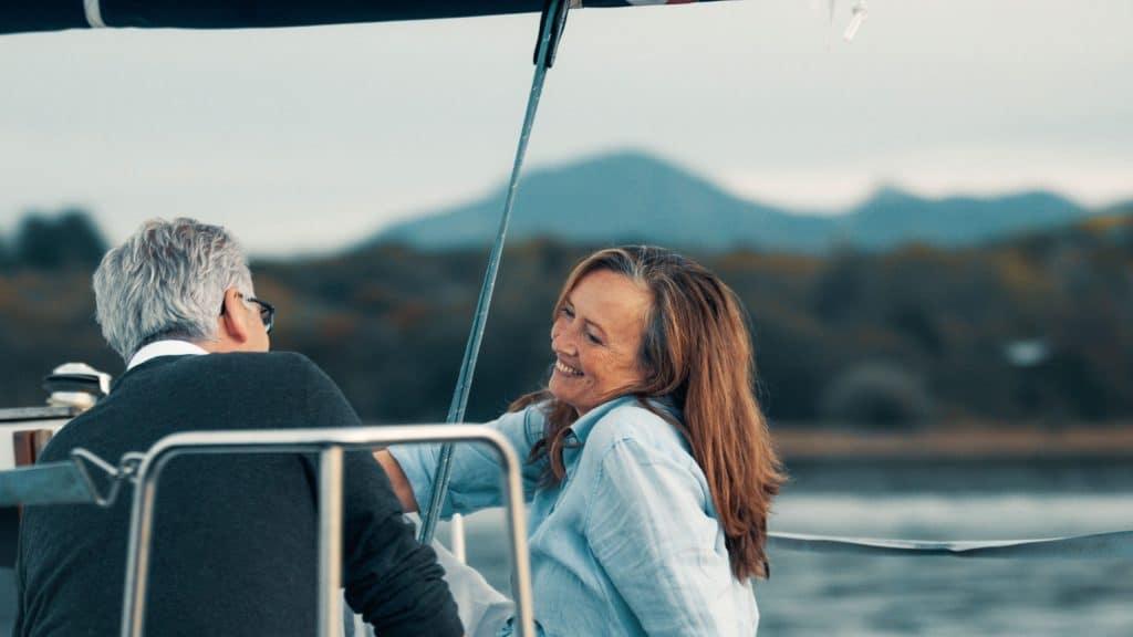 Ein Ehepaar sitzt sich auf einem Segelboot gegenüber, die Frau lacht, Chiemsee, sorgloses Leben im Alter, SofortRente Invest, Versicherungskammer Bayern, Werbespot, Erklärfilm, WINGMEN Media