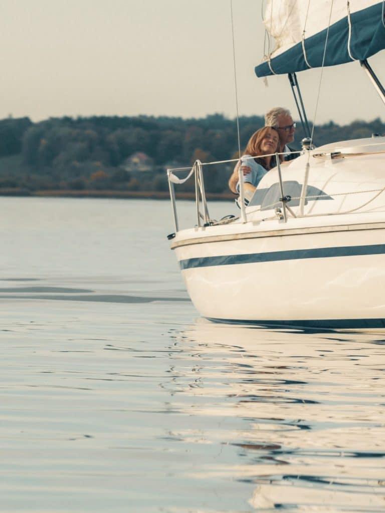 Ein Segelboot im Chiemsee auf dem ein Ehepaar Arm in Arm sitzt und die Fahrt genießt, bayrisches Meer, sorglos, SofortRente Invest, Versicherungskammer Bayern, Werbespot, Erklärfilm, WINGMEN Media