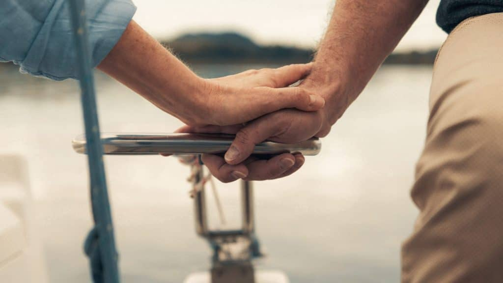 Detailaufnahme von den Händen eines Ehepaars, dass Händchen hält beim Segeln im Chiemsee, Liebe, sorglos im Alter, SofortRente Invest, Versicherungskammer Bayern, Werbespot, Erklärfilm, WINGMEN Media