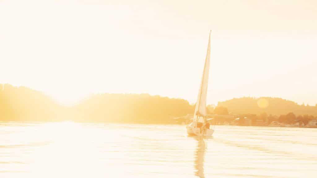 Ein Segelboot segelt durch den Chiemsee, Boot, Segeln, bayrisches Meer, High-key, Sonne, Lichtstimmung, Versicherungskammer Bayern, Werbespot, Erklärfilm, WINGMEN Media