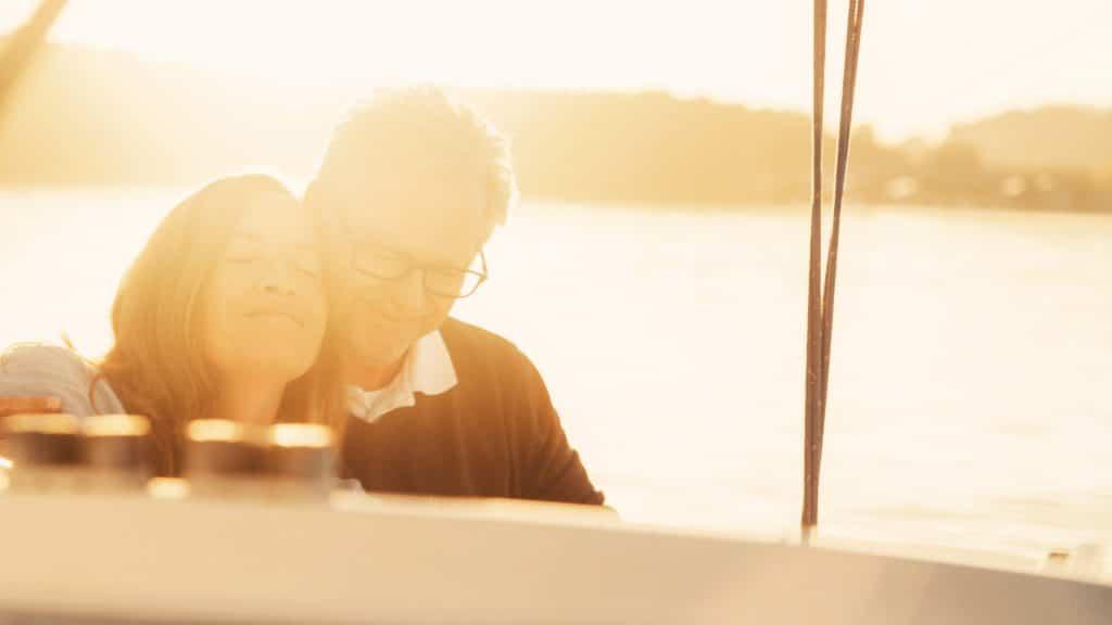 Ein lächelndes Ehepaar entspannt auf einem Segelboot im Chiemsee, Sofort Rente Invest, genießen, Versicherungskammer Bayern, Werbespot, Erklärfilm, WINGMEN Media