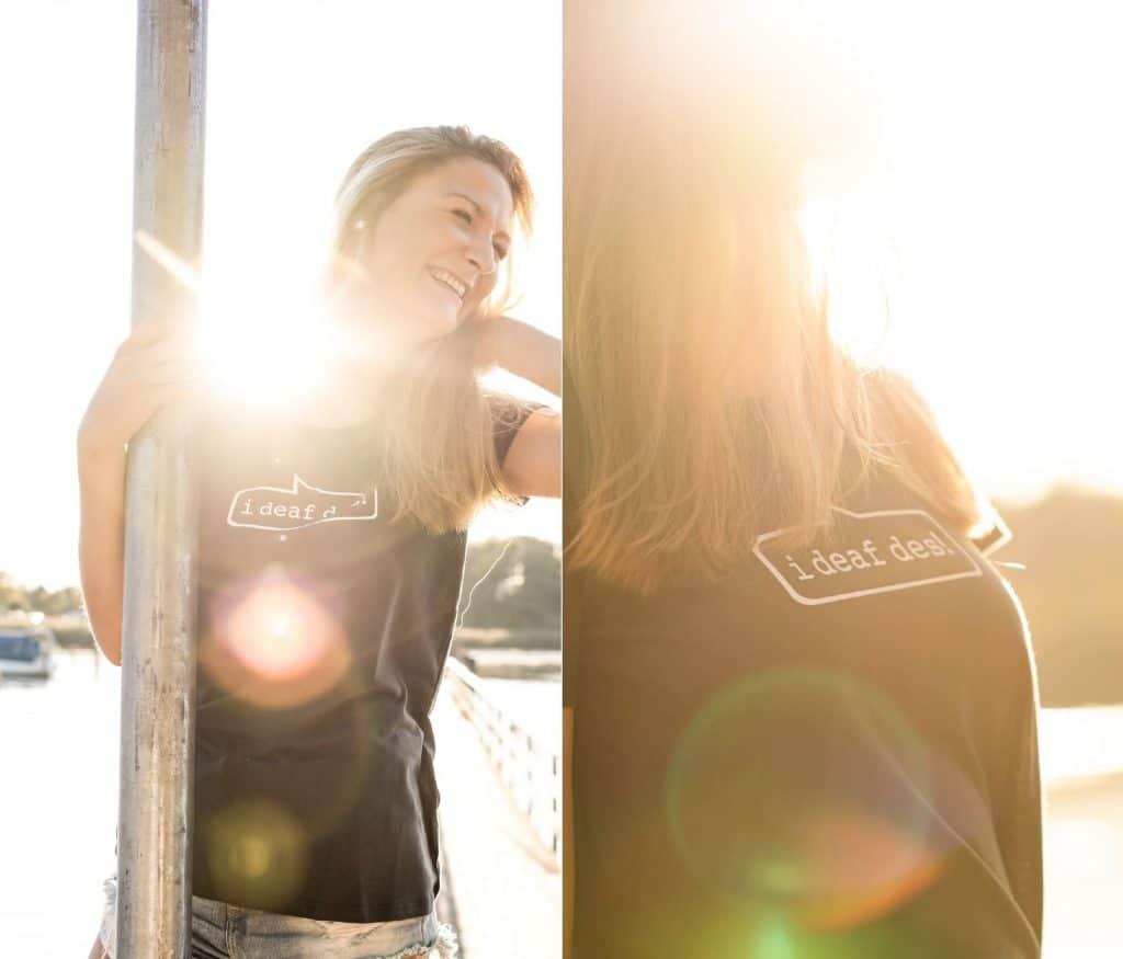 """Eine lachende Frau trägt ein """"i deaf des!"""" T-Shirt, Aufdruck, bayrisch, High-key, Lensflare, Chiemsee, bayrisches Meer, Servus Heimat GmbH, Produktfotografie, Lifestylefotografie, WINGMEN Media"""