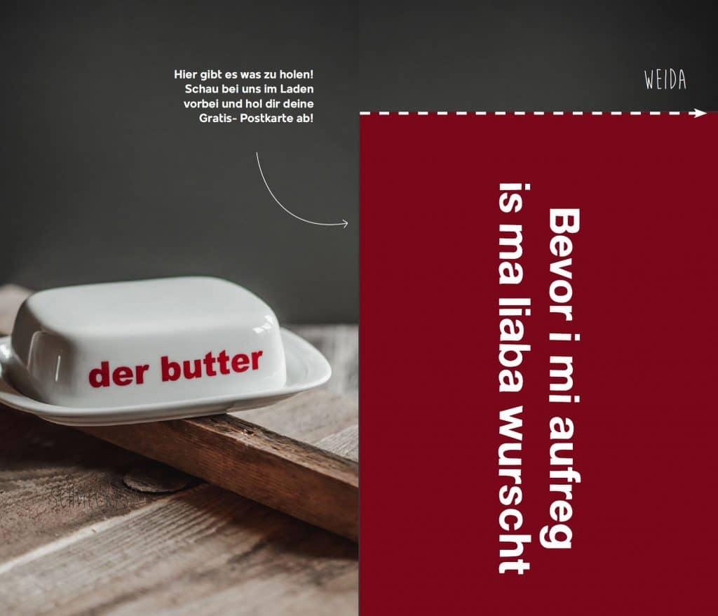 Eine weiße Butterdose mit roter der Butter Aufschrift, und rote Postkarte mit Spruch, Andenken und Mitbringsel, moderne bayerische Geschenkeparadies, Servus Heimat GmbH, Produktfotografie, Flyer, WINGMEN Media