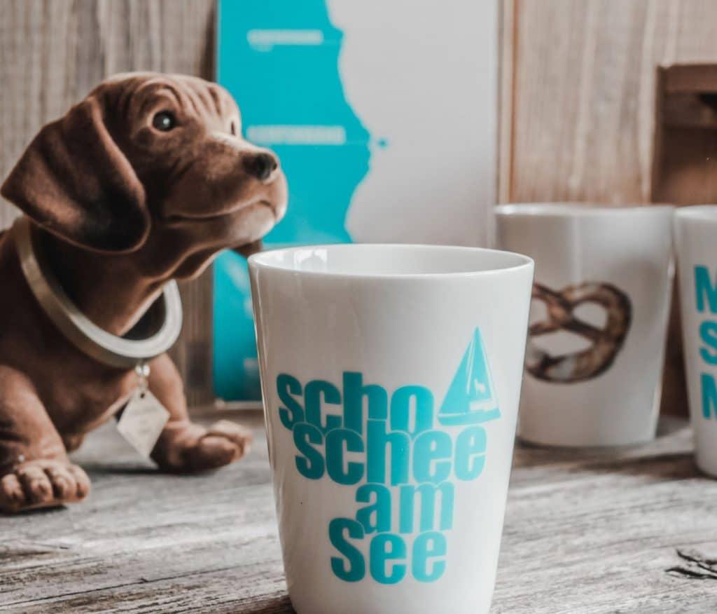 Eine weiße Tasse mit scho schee am See Aufdruck, Schrift, Segelboot, Wackeldackel im Hintergrund, Mitbringsel und Andenken, Servus Heimat GmbH, Produktfotografie, Flyer, WINGMEN Media