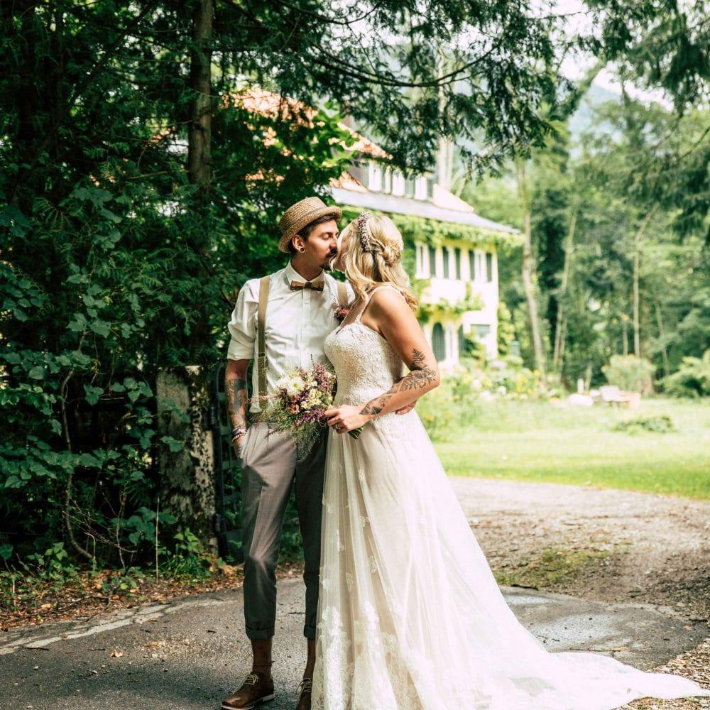 Ein Brautpaar küsst sich draußen auf dem Weg zu einem Haus, Schleppe, Brautstrauß, Hochzeit, Event Fotografie, WINGMEN Media