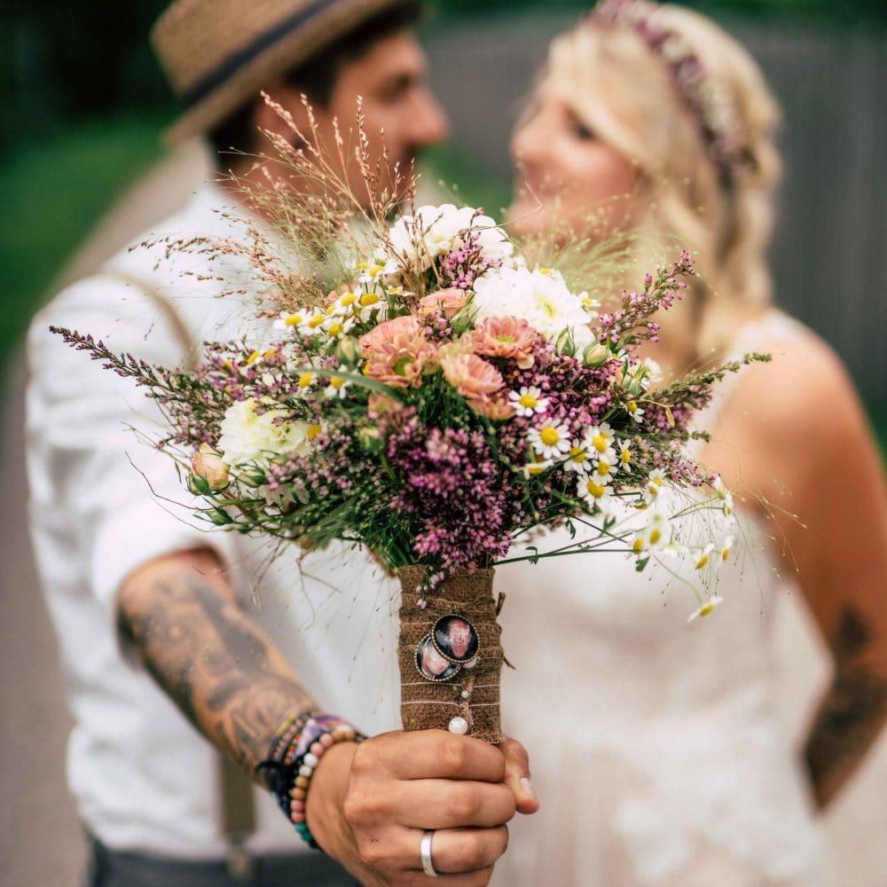 Ein Brautpaar, Bräutigam hält den Brautstrauß nach vorne, Blumen, Ehering, Hochzeit, Event Fotografie, WINGMEN Media