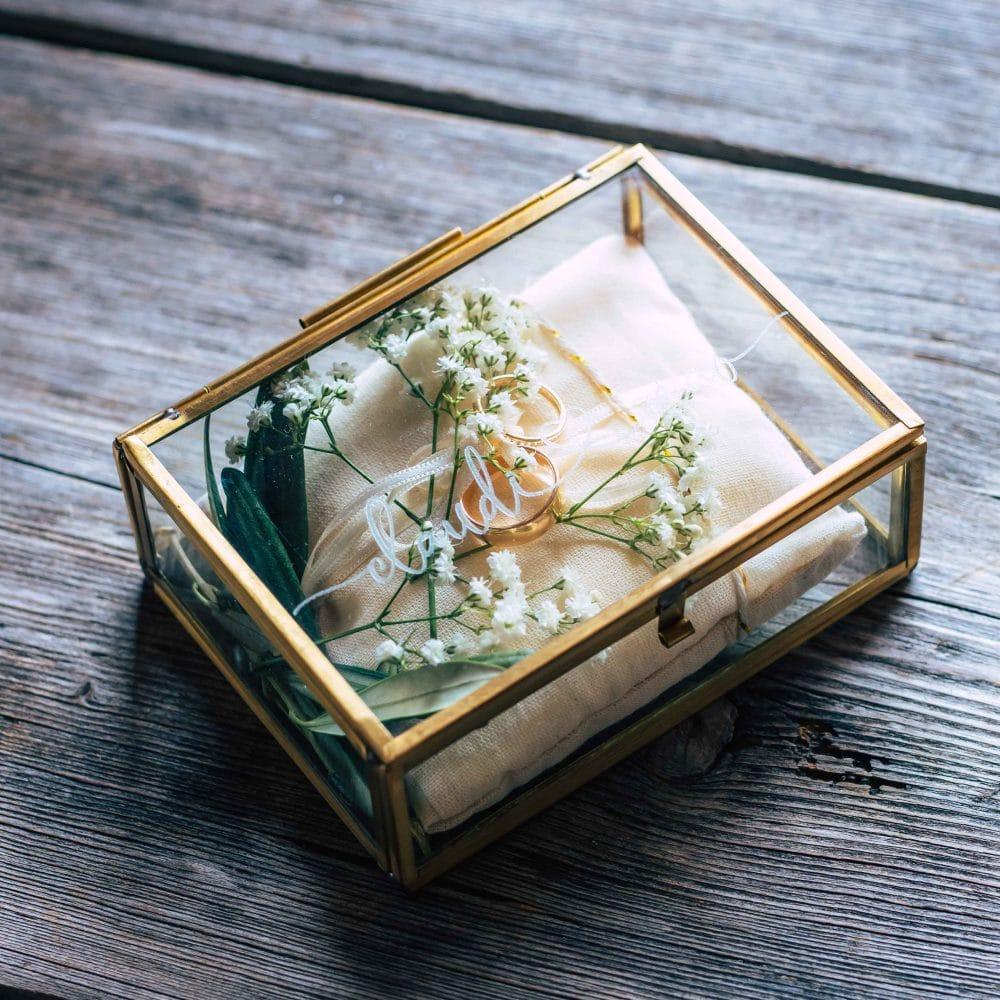 Die Eheringe der Brautpaars in einer Glas Schatulle, Ringe, Hochzeit, Event Fotografie, WINGMEN Media