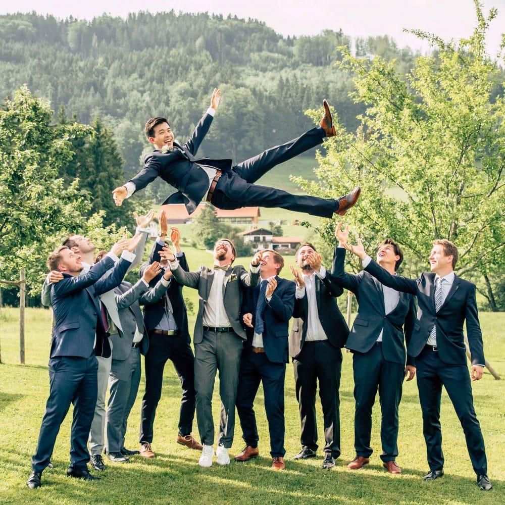 Ein Bräutigam wird von seinen Freunden hoch geworfen draußen auf einer Wiese, alle lachen, blauer Himmel, Event Fotografie, WINGMEN Media