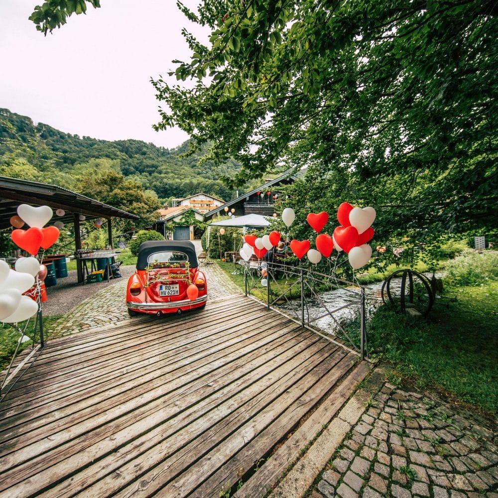 Ein roter VW Käfer als Hochzeitswagen fährt über eine Brücke, Herzluftballons, Hochzeit, Event Fotografie, WINGMEN Media