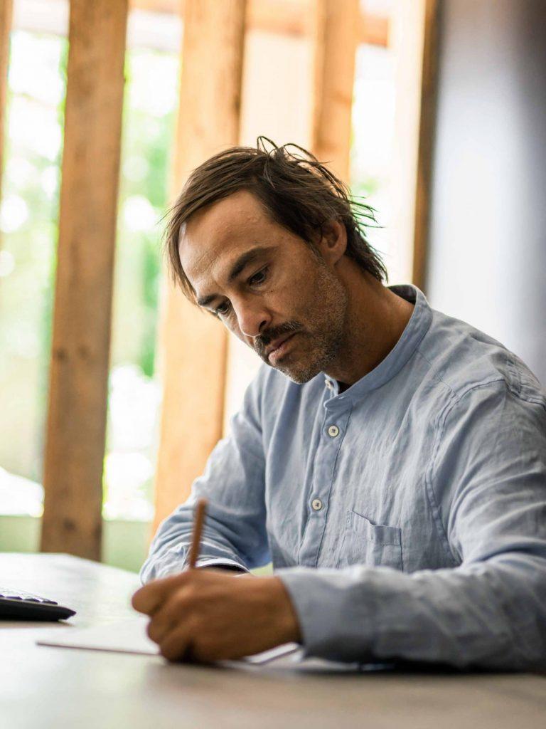 Ein sitzender Mann beim Schreiben, Planen, Landschaftsarchitekt, Friedhof, Friedhofs-Kompetenz_Zentrum GmbH & Co. KG, Unternehmensfotografie, WINGMEN Media