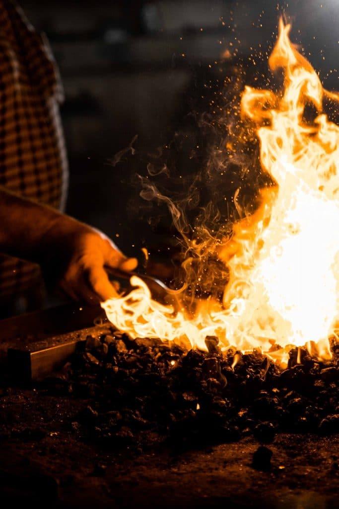 Nahaufnahme einer Hand und Flamme bei Schmied Arbeiten für Friedhof, Eisen, Stahl, fkz, Friedhofs-Kompetenz-Zentrum GmbH & Co. KG, Unternehmensfotografie, WINGMEN Media