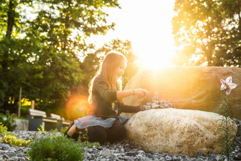 Ein junges Mädchen sitzt auf dem Boden eines Naturbestattungen Gedenkwalds und baut einen Turm aus Steinen, lensflare, High-key, Friedhofs-Kompetenz-Zentrum GmbH & Co. KG, Unternehmensfotografie, WINGMEN Media