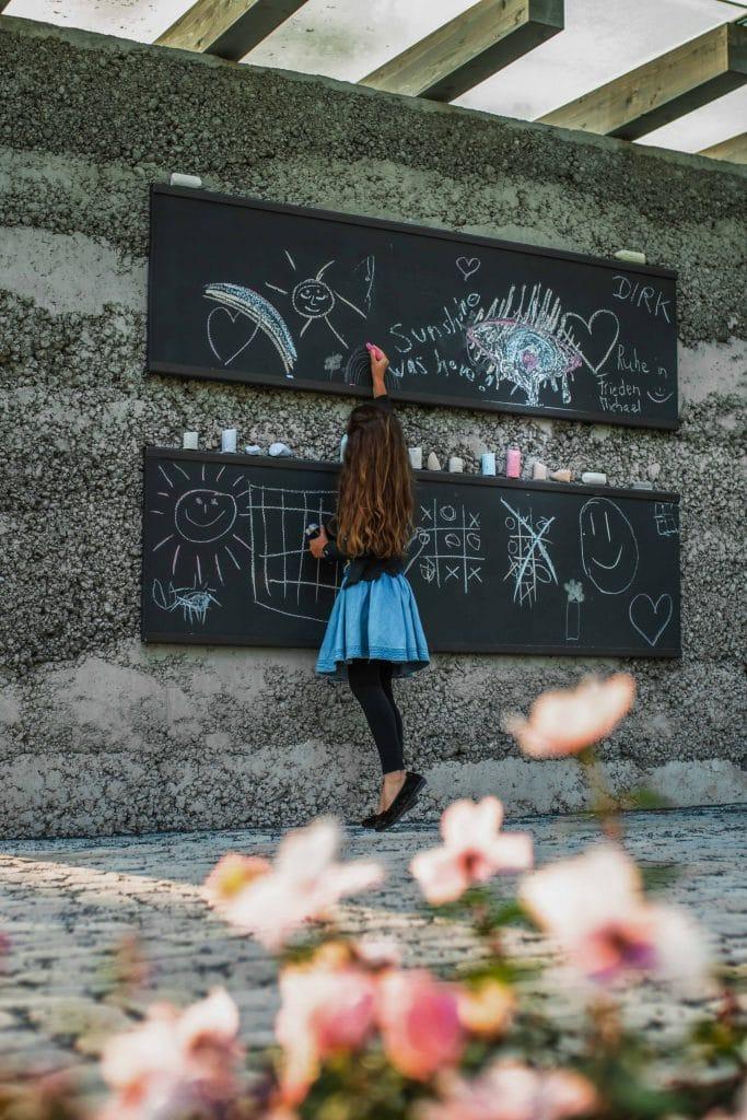 Ein Mädchen malt mit Kreide auf eine Tafel an einer Steinwand in einem Naturbestattungen Gedenkwald, fkz, Friedhofs-Kompetenz-Zentrum GmbH & Co. KG, Unternehmensfotografie, WINGMEN Media