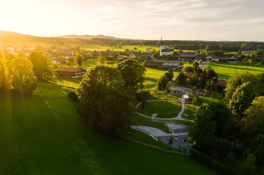 Drohnenaufnahme eines Naturbestattungen Gedenkwalds, Landschaft, grüne Wiese, lensflare, Friedhofs-Kompetenz-Zentrum GmbH & Co. KG, Unternehmensfotografie, Social Media, WINGMEN Media