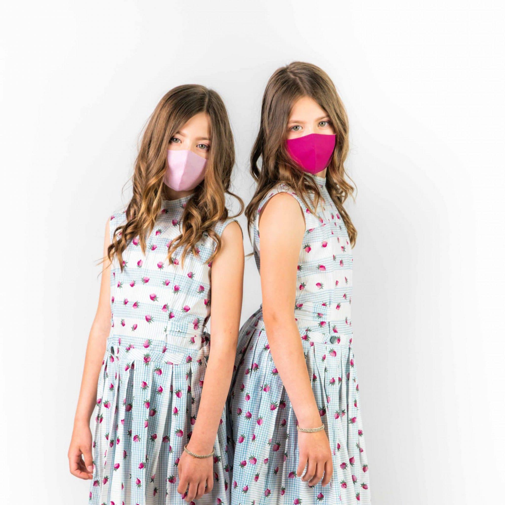 Studioaufnahme von zwei Mädchen, Zwillingen, in Kleider, beide tragen Masken in Pink und Rosa, Smile for Change Maske, My Blossom, Produktfotografie, WINGMEN Media