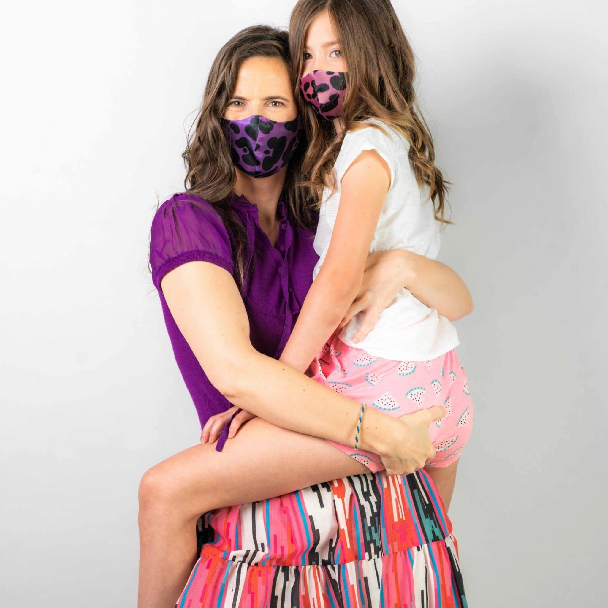 Studioaufnahme einer Frau mit ihrer Tochter auf dem Arm, beide tragen Masken mit Leo Print, Smile for Change Maske, My Blossom, Produktfotografie, WINGMEN Media