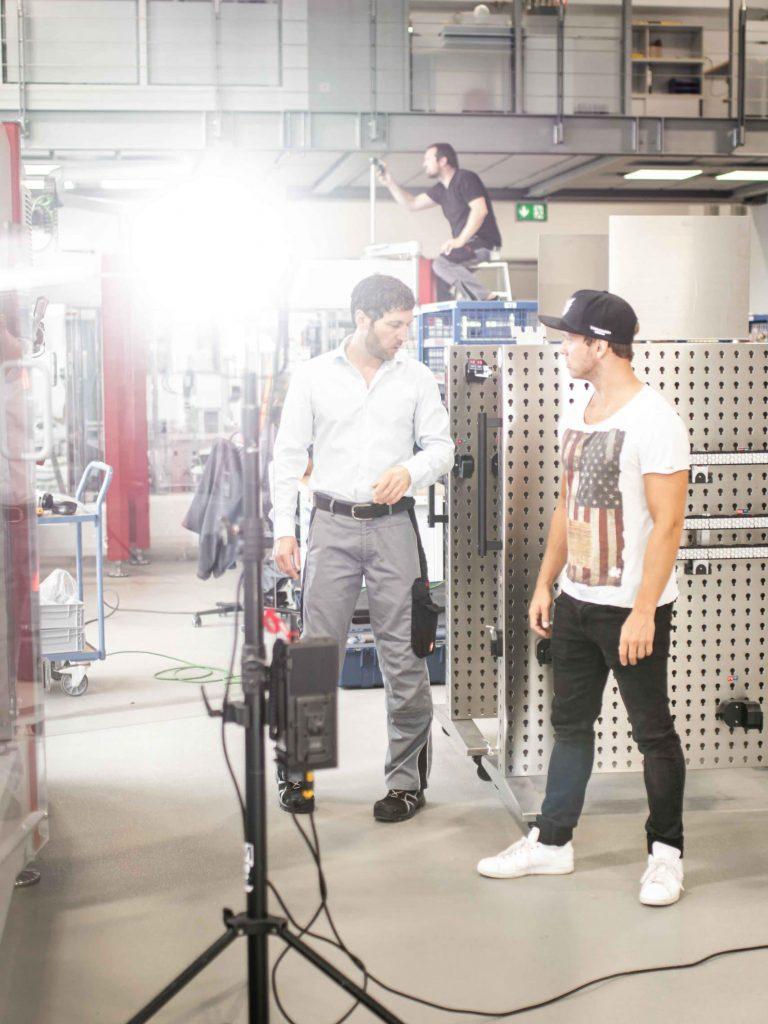 Regie und Darsteller bei Besprechung während Dreh, Aputure COB 300d, High-key, Verpackungsmaschinen, Somic GmbH, Behind The Scenes Fotografie, WINGMEN Media