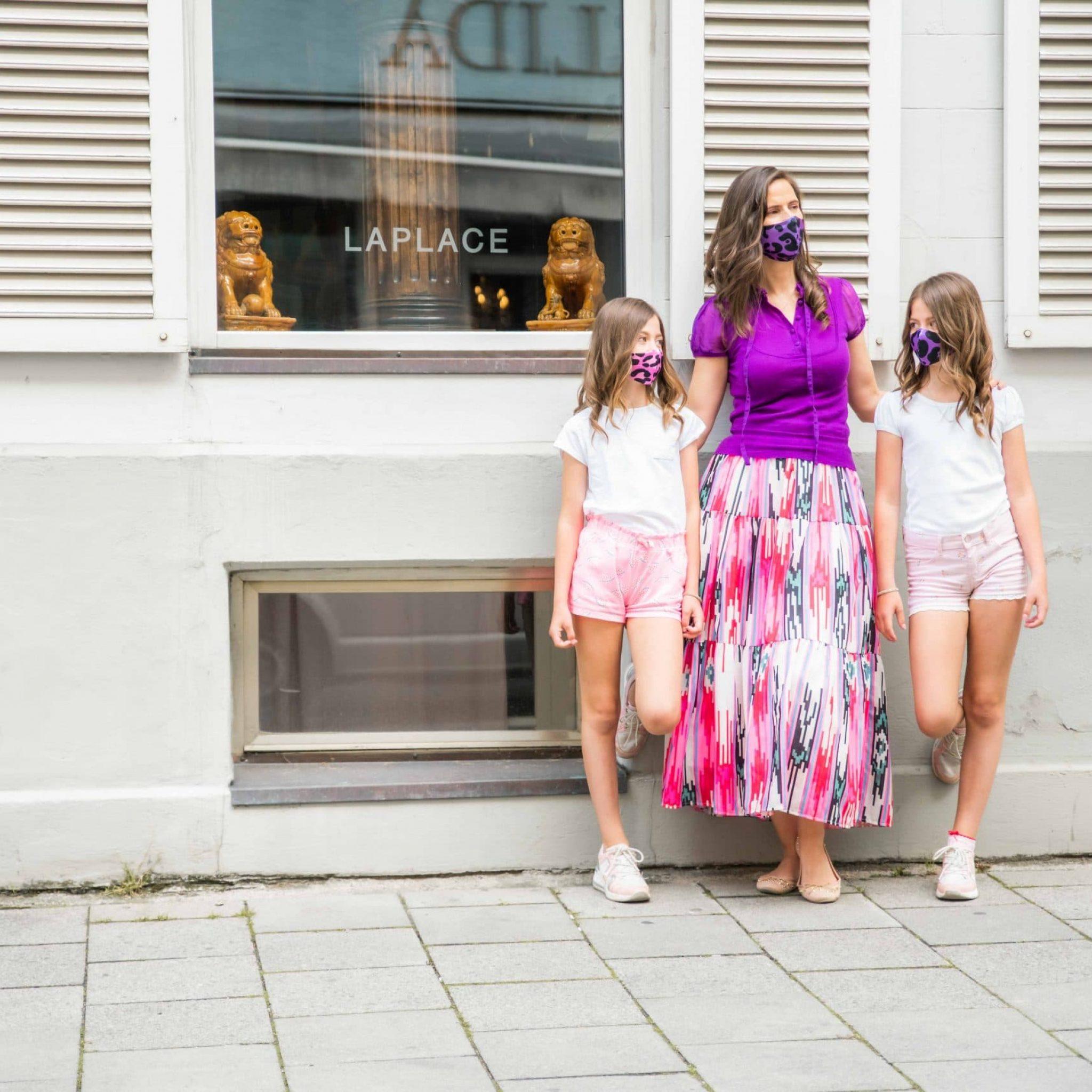 Eine Mutter und ihre zwei Töchter tragen Mutter-Tochter Kombi Masken mit Leo Print, Smile for Change Masken, My Blossom, Produktfotografie, Lifestylefotografie, WINGMEN Media