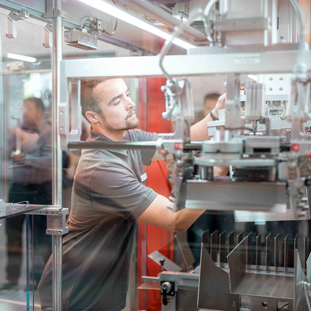 Mitarbeiterfotografie eines jungen Mannes bei Arbeit an Verpackungsmaschine, Somic GmbH, Unternehmensfotografie, WINGMEN Media