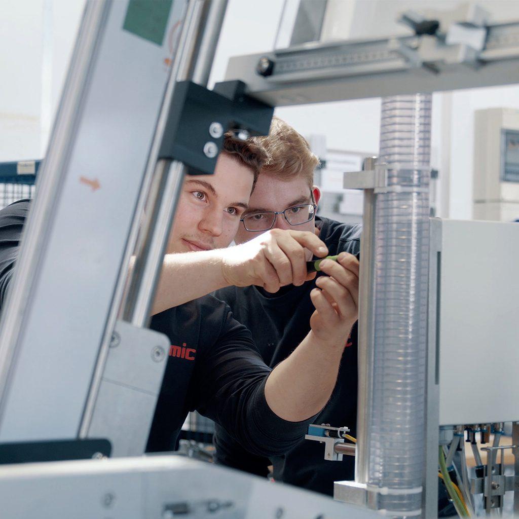 Zwei junge Männer bei der Arbeit an einer Maschine, Ausbildung zum Elektriker für Betriebstechnik, Verpackungsmaschinen, SOMIC, Recruitingfilm, WINGMEN Media