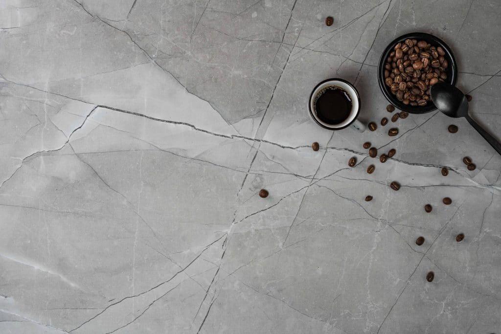 Schüssel mit Kaffeebohnen neben einer Tasse Kaffee auf Dekor mit Steinoptik, Schattdecor, Produktfotografie, WINGMEN Media