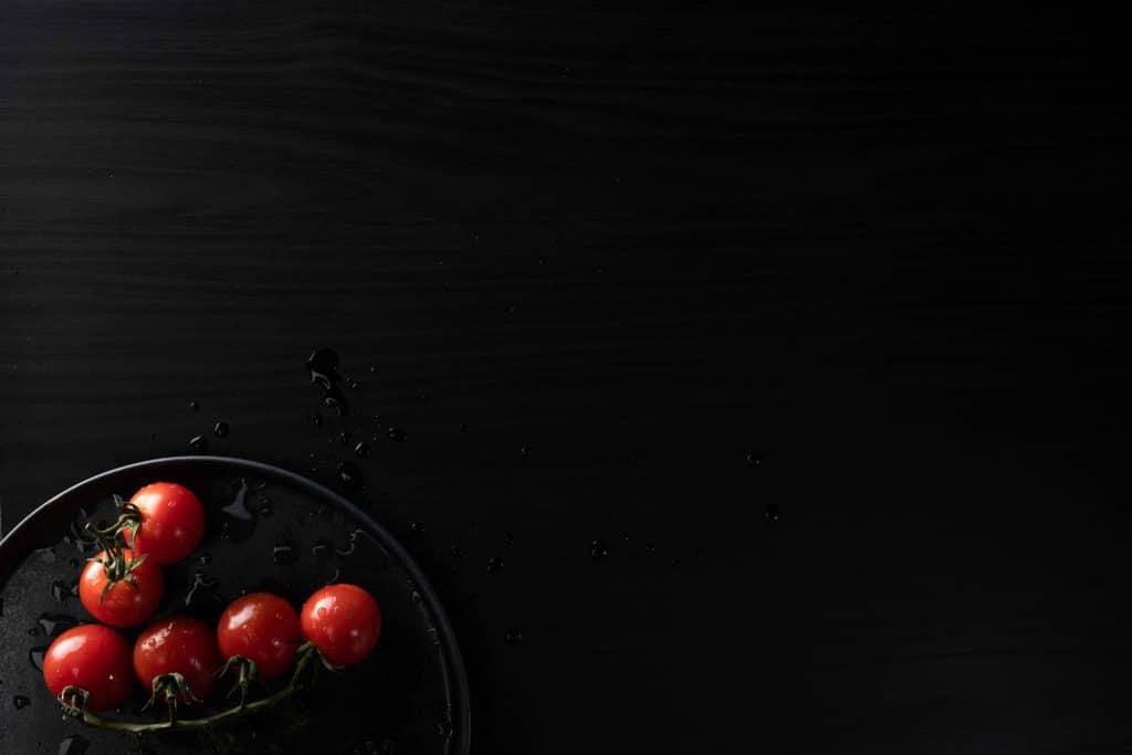 Teller mit Tomaten auf feuchtebeständigem dunklen Dekor mit Holzoptik, Holzdekor, Schattdecor, Produktfotografie, WINGMEN Media