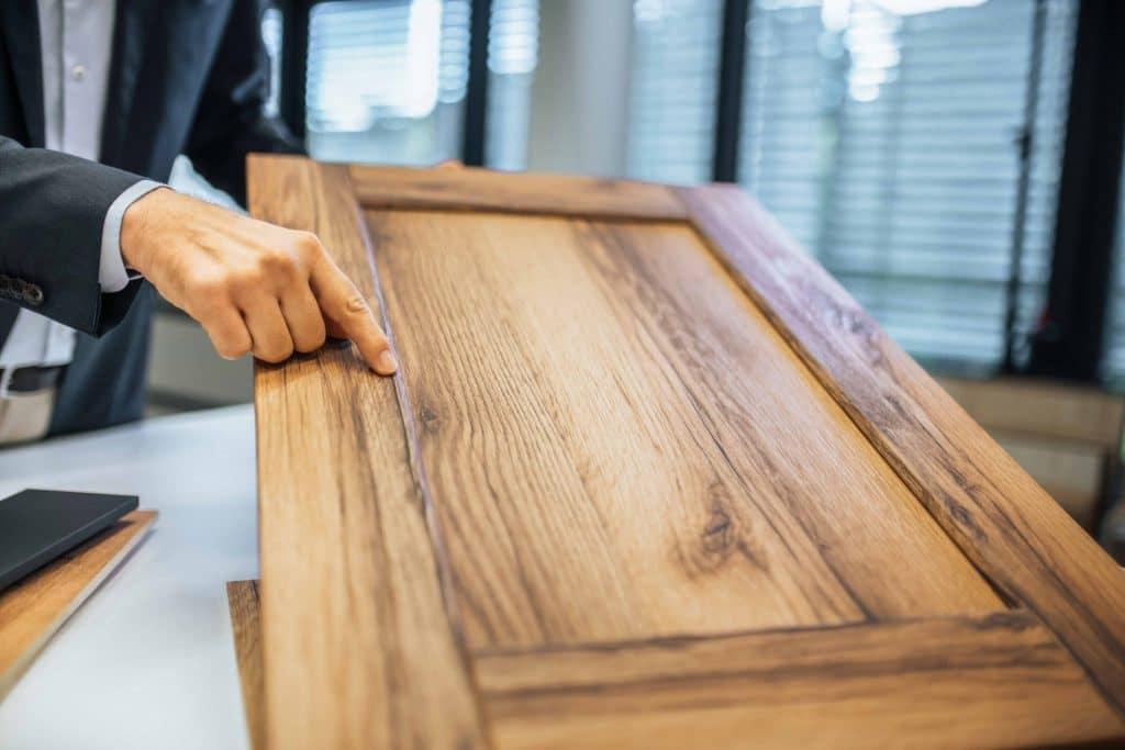 Hand die auf Detail Übergang von hellem Dekor mit Holzoptik zeigt, Schattdecor, Unternehmensfotografie, Produktfotografie, WINGMEN Media