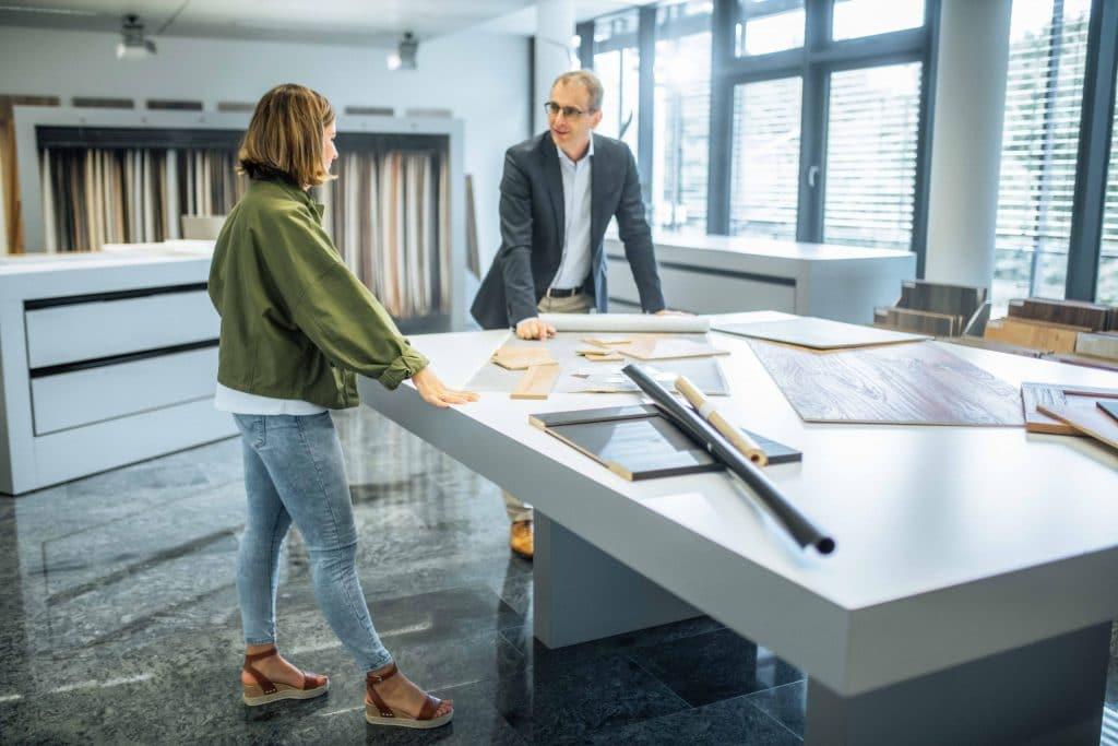zwei Personen bei Entwicklung von Holzdekoren an einem großen Tisch, Schattdecor, Unternehmensfotografie, Behind The Scenes Fotografie, WINGMEN Media